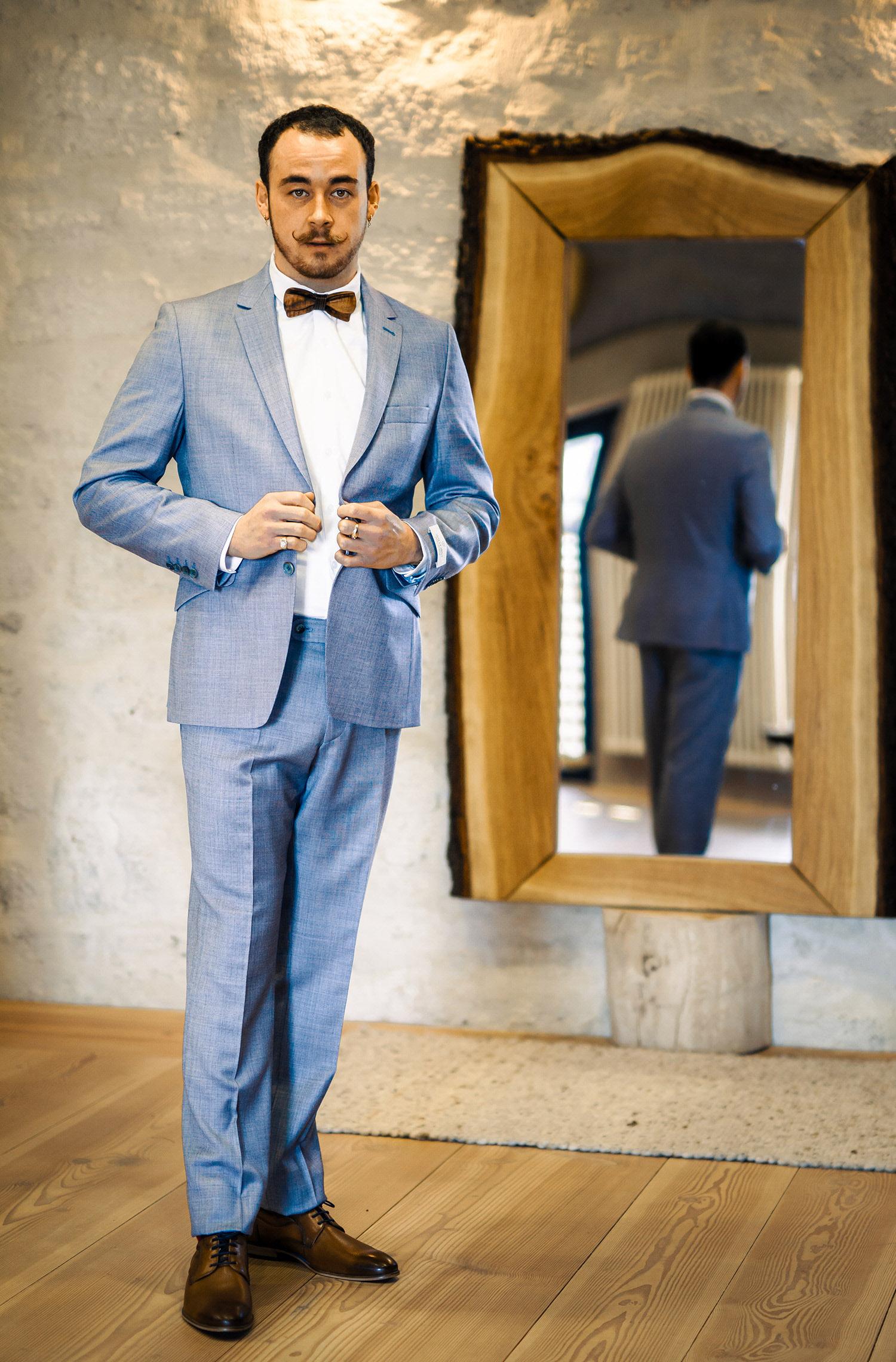 Ein Mann trägt einen Hochzeitsanzug von Wilvorst Green Wedding in Aubergine