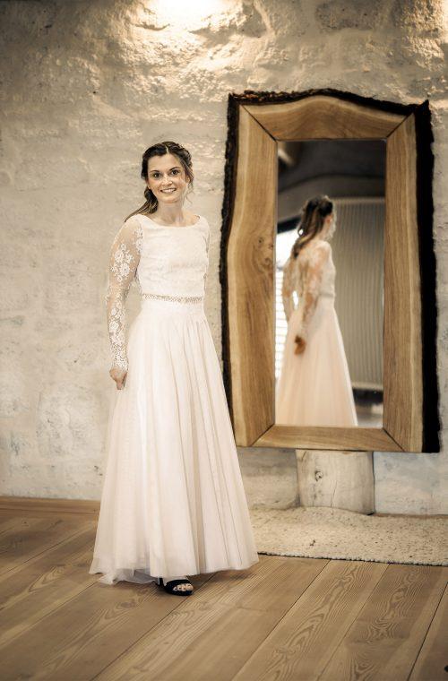 Eine Frau trägt das Spitzenoberteil S.Luxat von Kleider machen Bräute