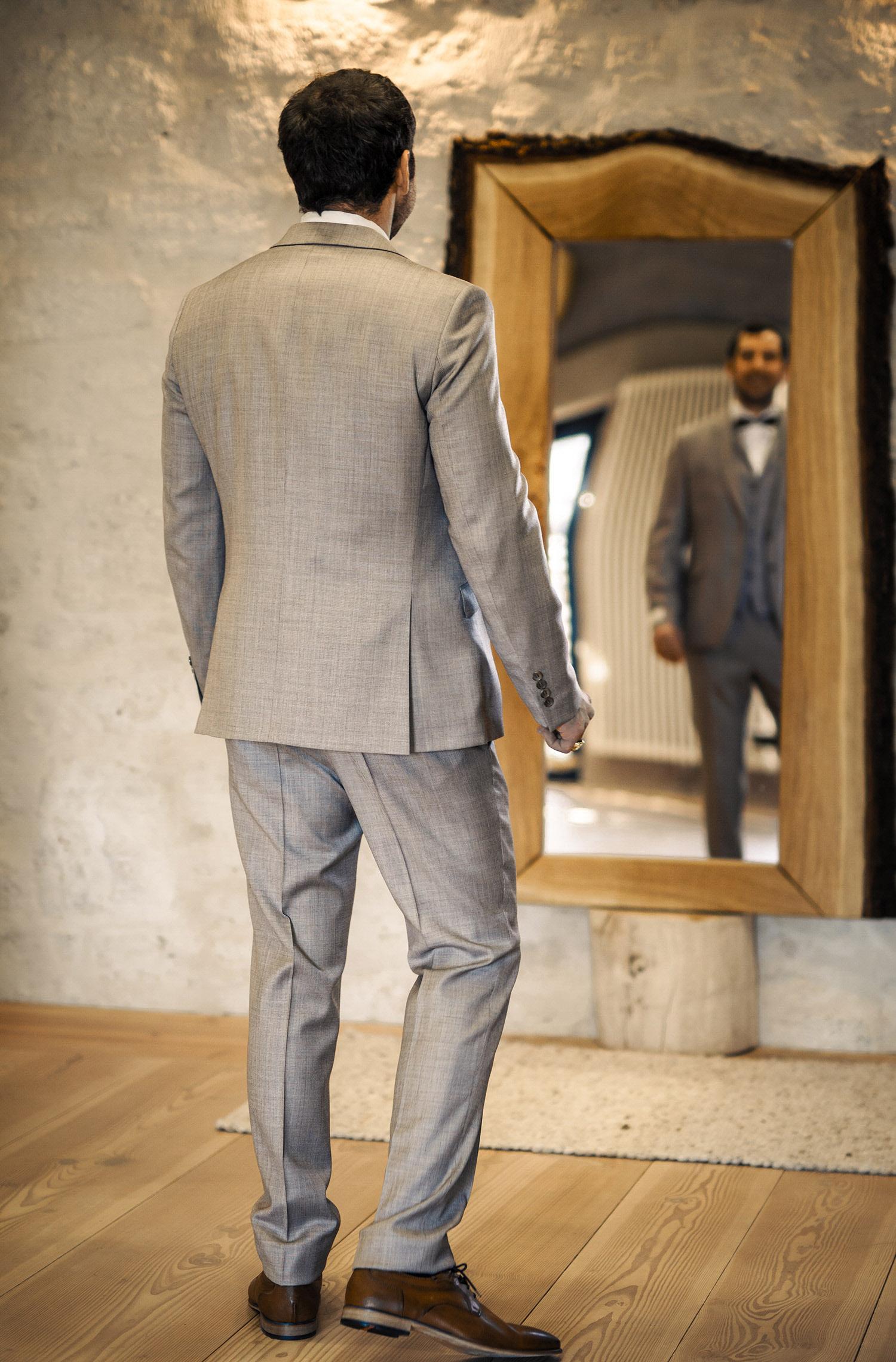 Ein Mann trägt einen Hochzeitsanzug von Wilvorst Green Wedding in Beige