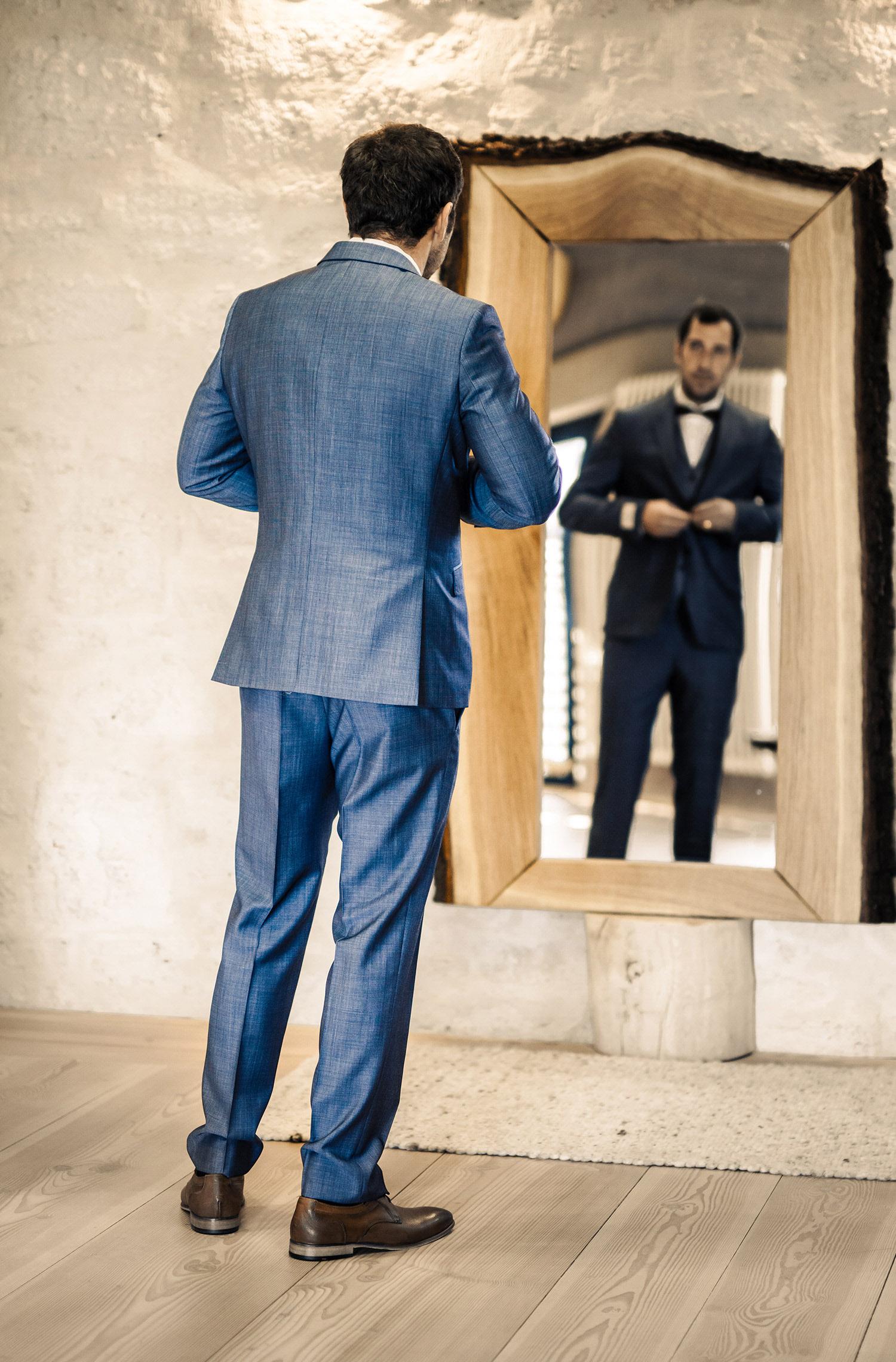 Ein Mann trägt einen Hochzeitsanzug von Wilvorst Green Wedding in Dunkelblau