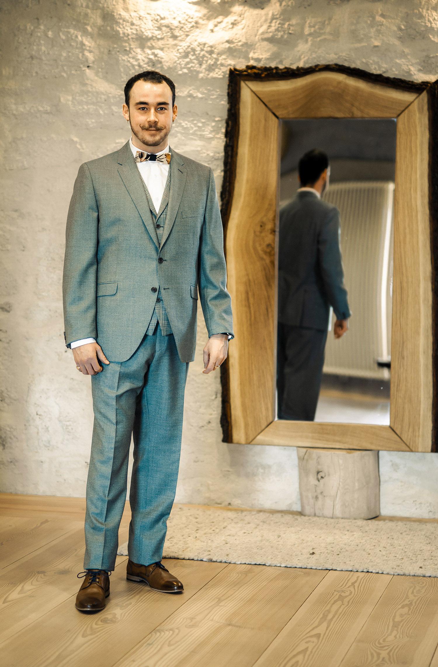 Ein Mann trägt einen Hochzeitsanzug von Wilvorst Green Wedding in Grün