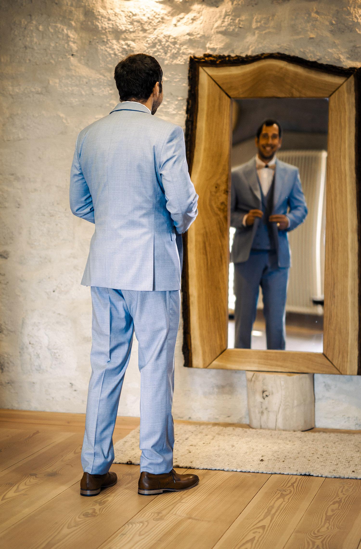 Ein Mann trägt einen Hochzeitsanzug von Wilvorst Green Wedding in Hellblau