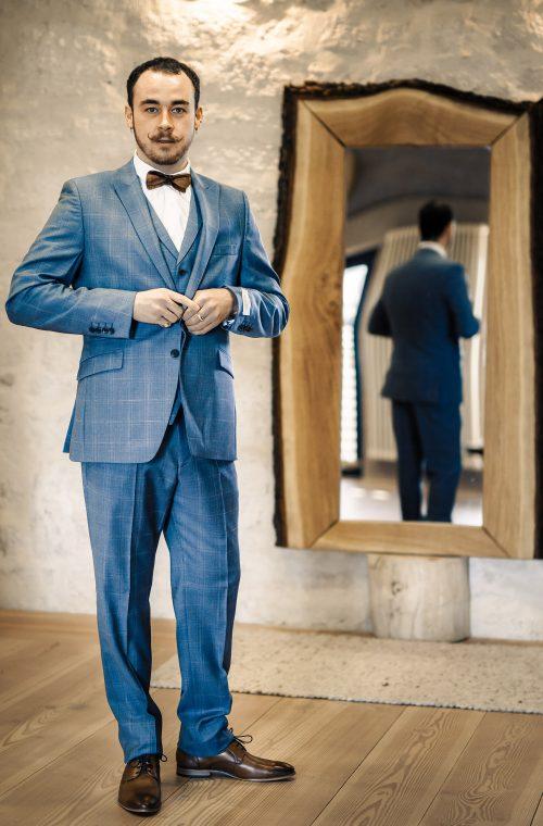 Ein Mann trägt einen Hochzeitsanzug von Wilvorst Green Wedding mit Karo